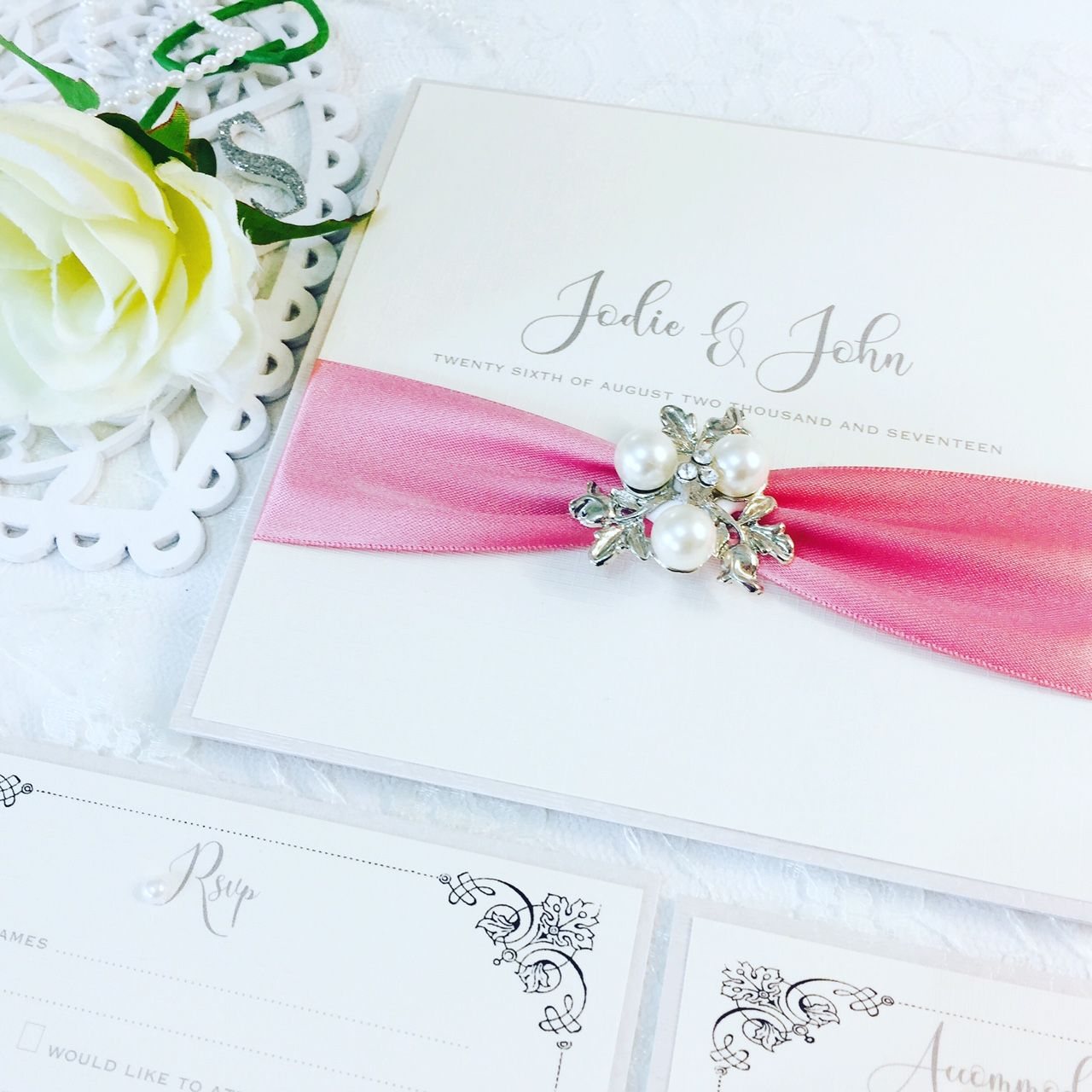 Boxed vintage style wedding invitations with ribbon and brooch