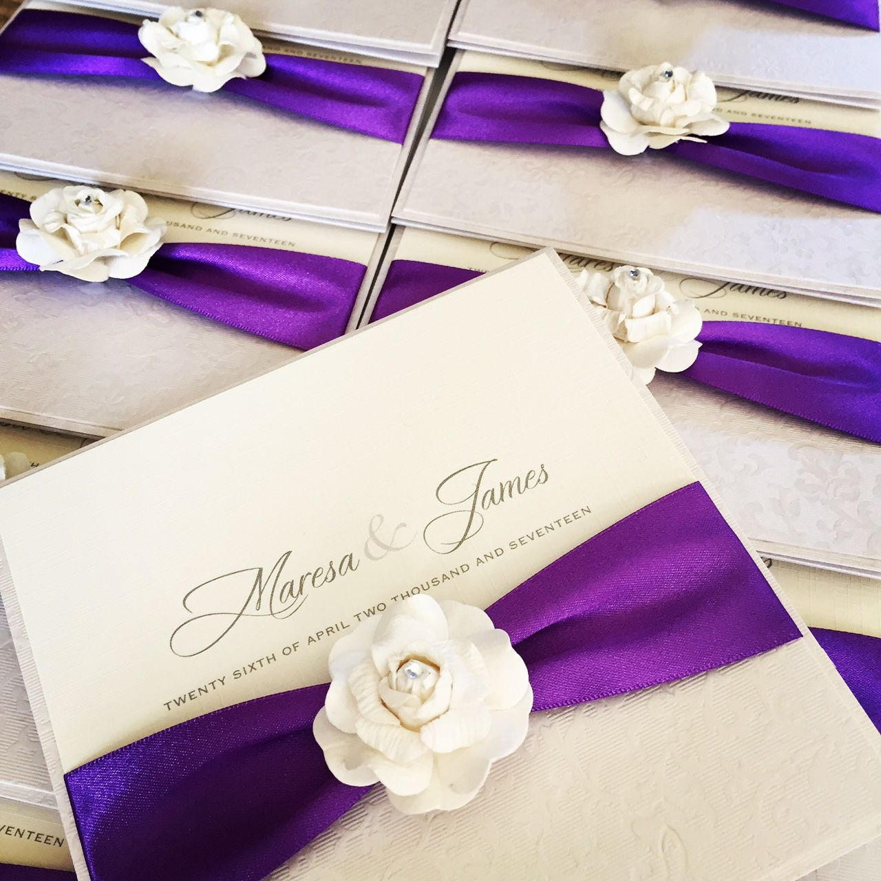 Rose themed wedding invitations with ivory roses and ribbons