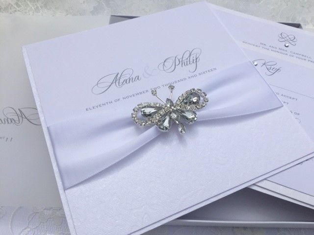 white wedding invitations with butterfly brooch
