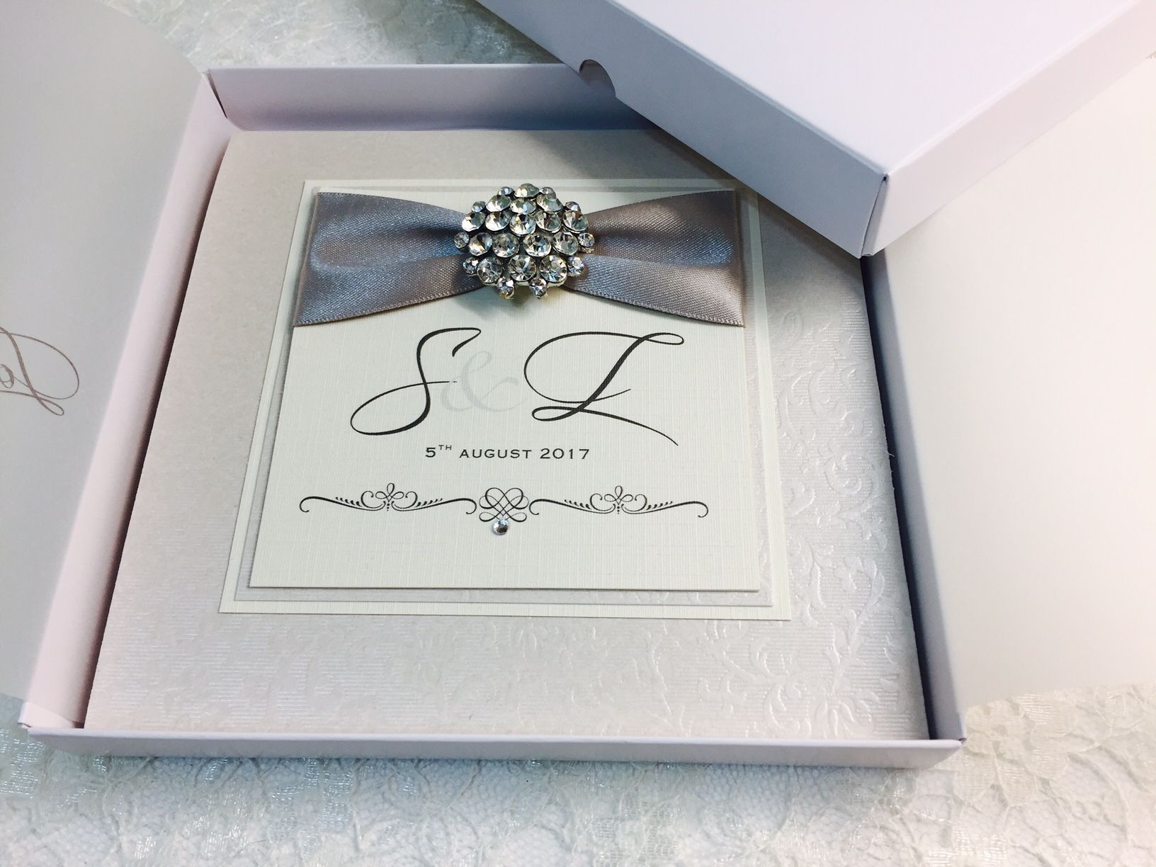 boxed monogram invitation with silver ribbon and diamante brooch