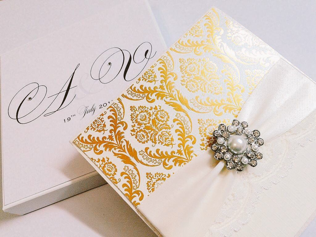 boxed invitation in gold and ivory with pearl brooch