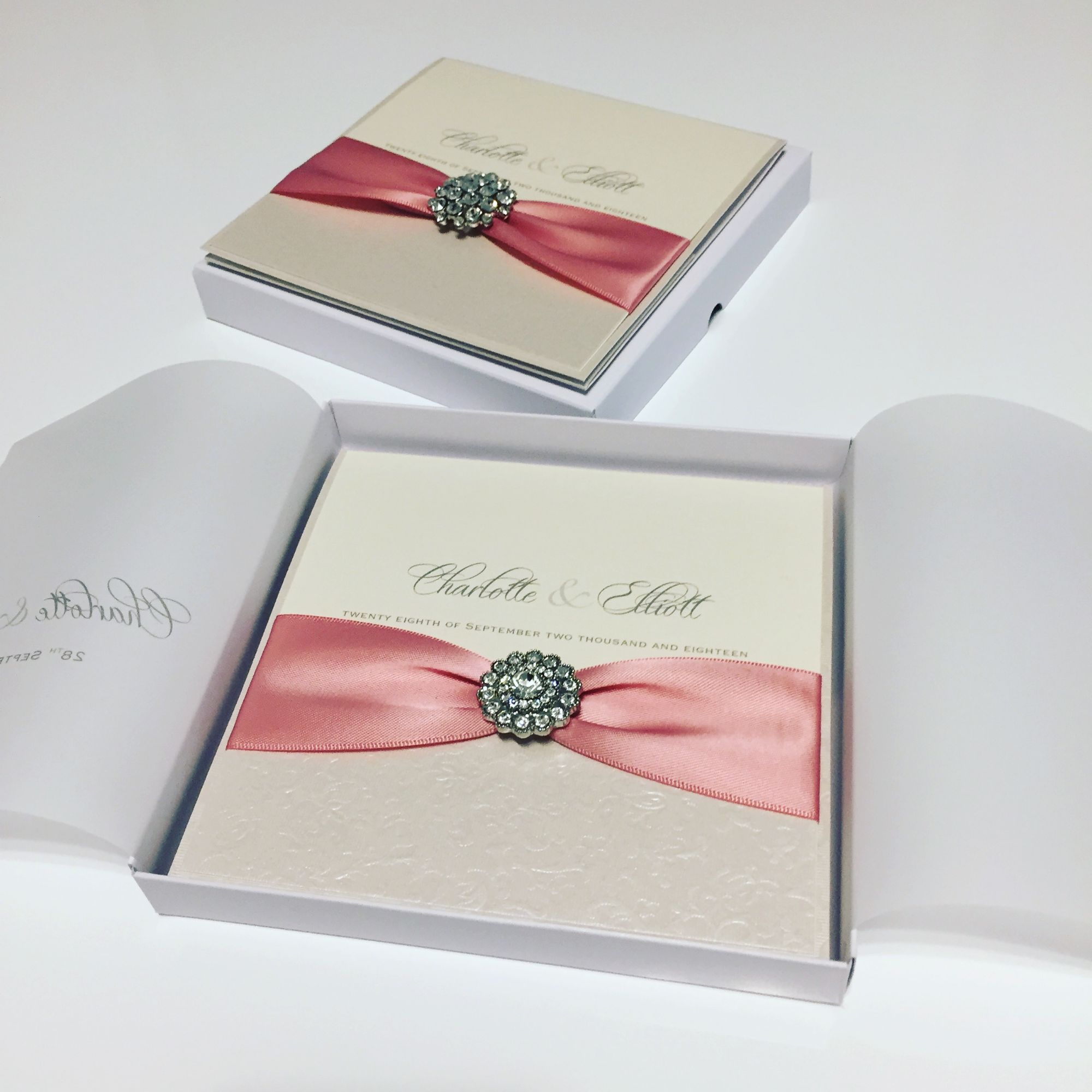 Boxed wedding invitations with dusky pink ribbon and vintage crystal brooch
