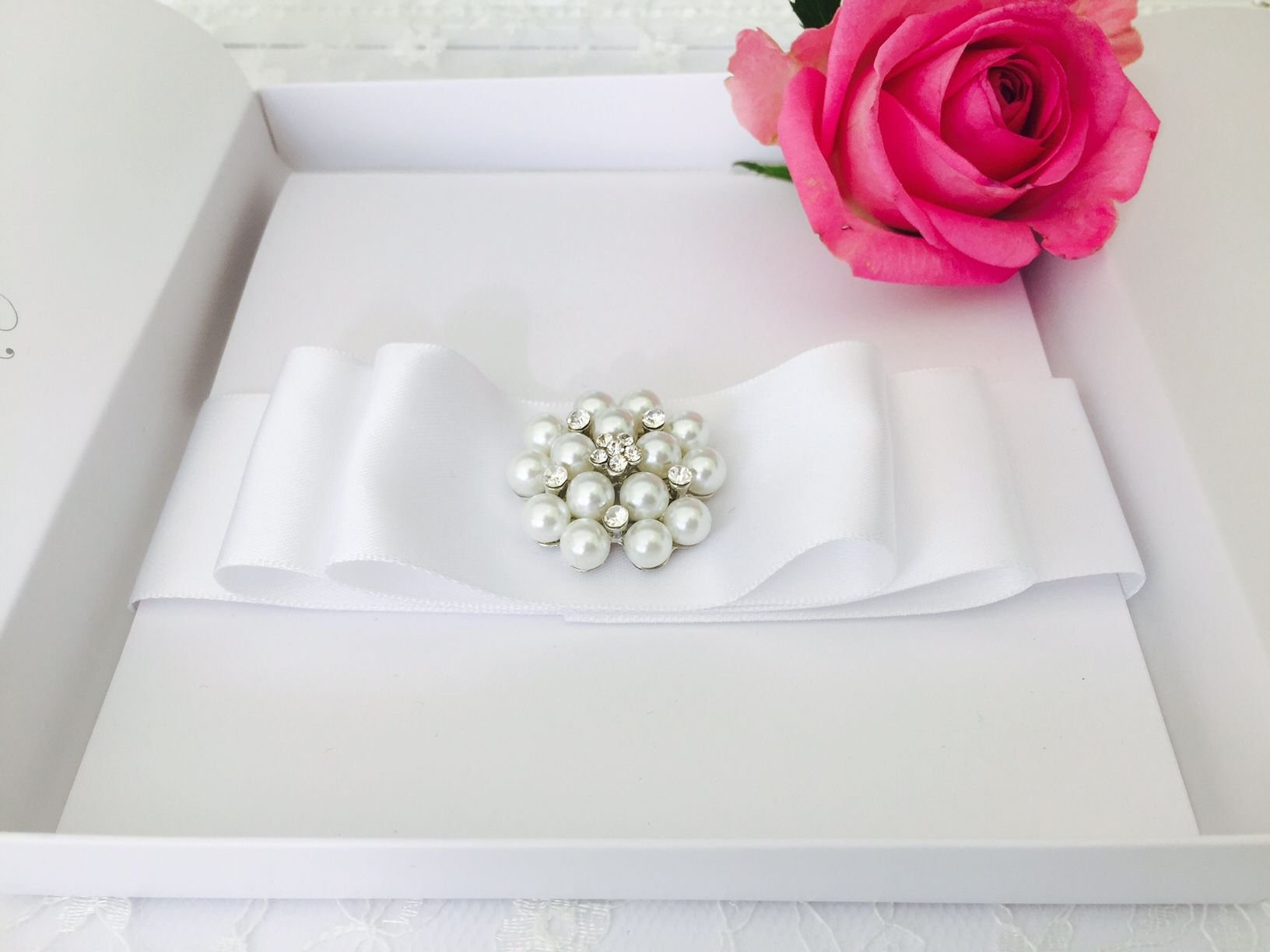 White boxed wedding invitation with elegant pearl brooch