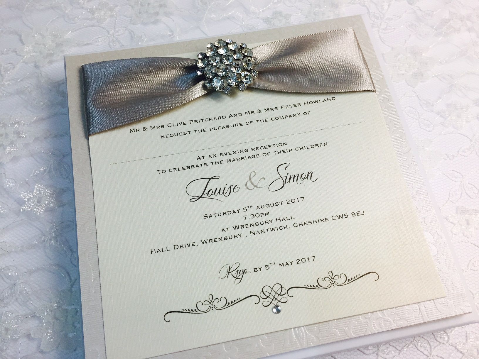 postcard style invitation with crystal brooch and silver ribbon