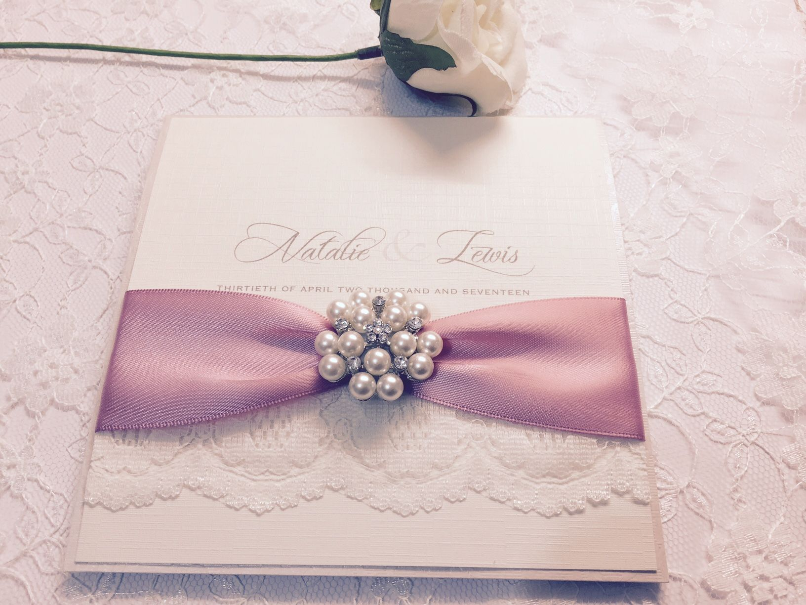 Luxury lace invitation with a dusky pink ribbon and vintage brooch