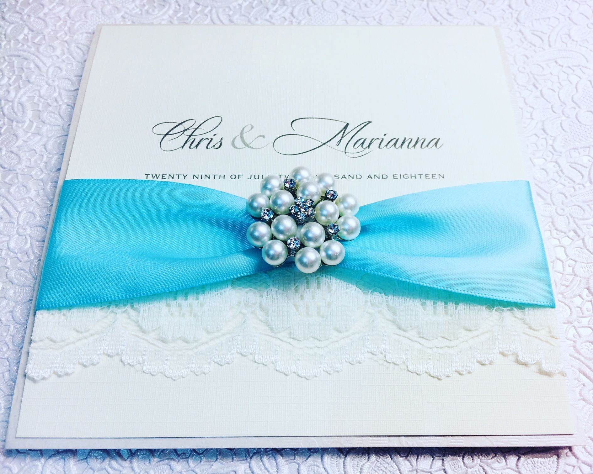 Boxed lace pocket fold invitations with turquoise blue ribbon and brooch