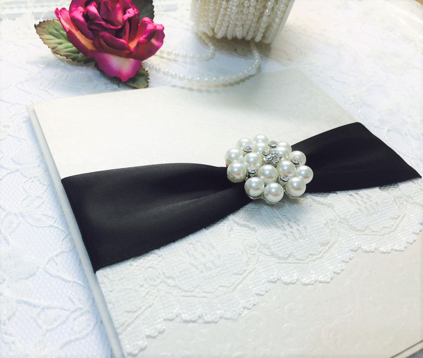 Boxed luxury lace invitation with black satin ribbon and brooch