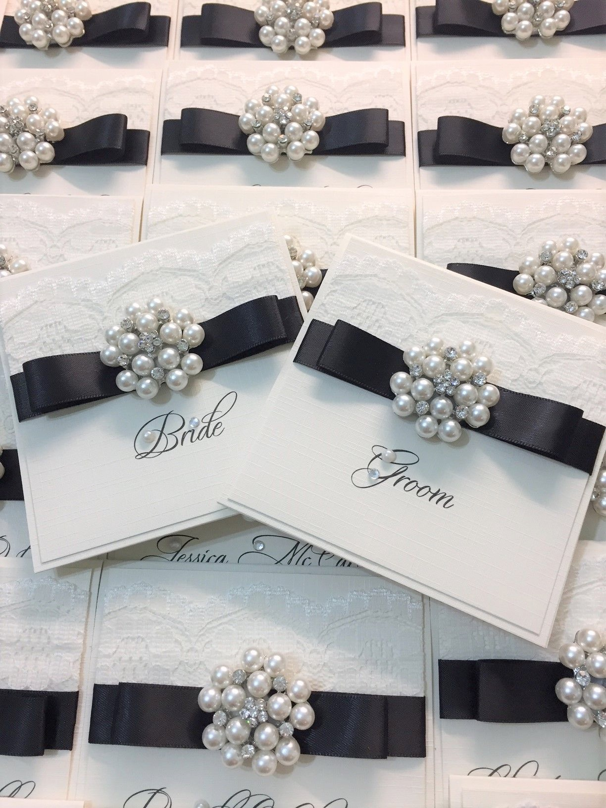 place name cards with brooch lace and black ribbon bow