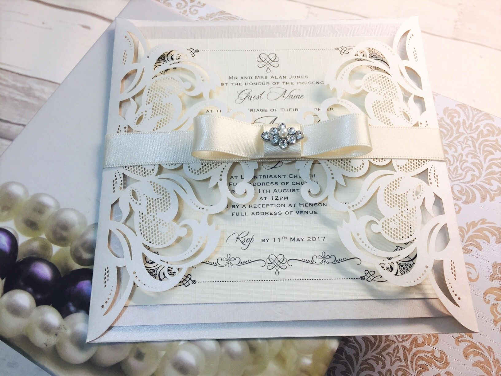 Luxury boxed wedding invitations designed with beautiful brooches and gorgeous ribbons and bows in a wide range of designs