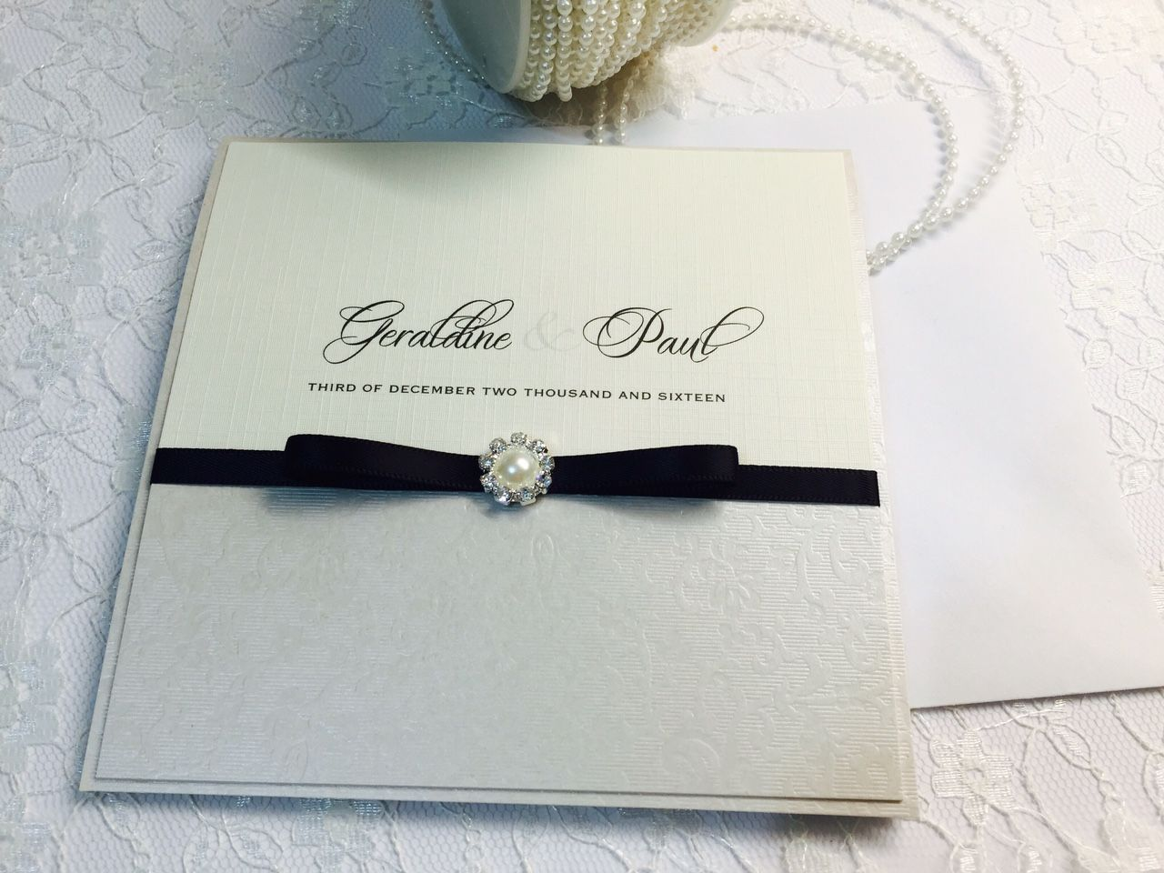 Black and ivory invitation with small round pearl and black ribbon