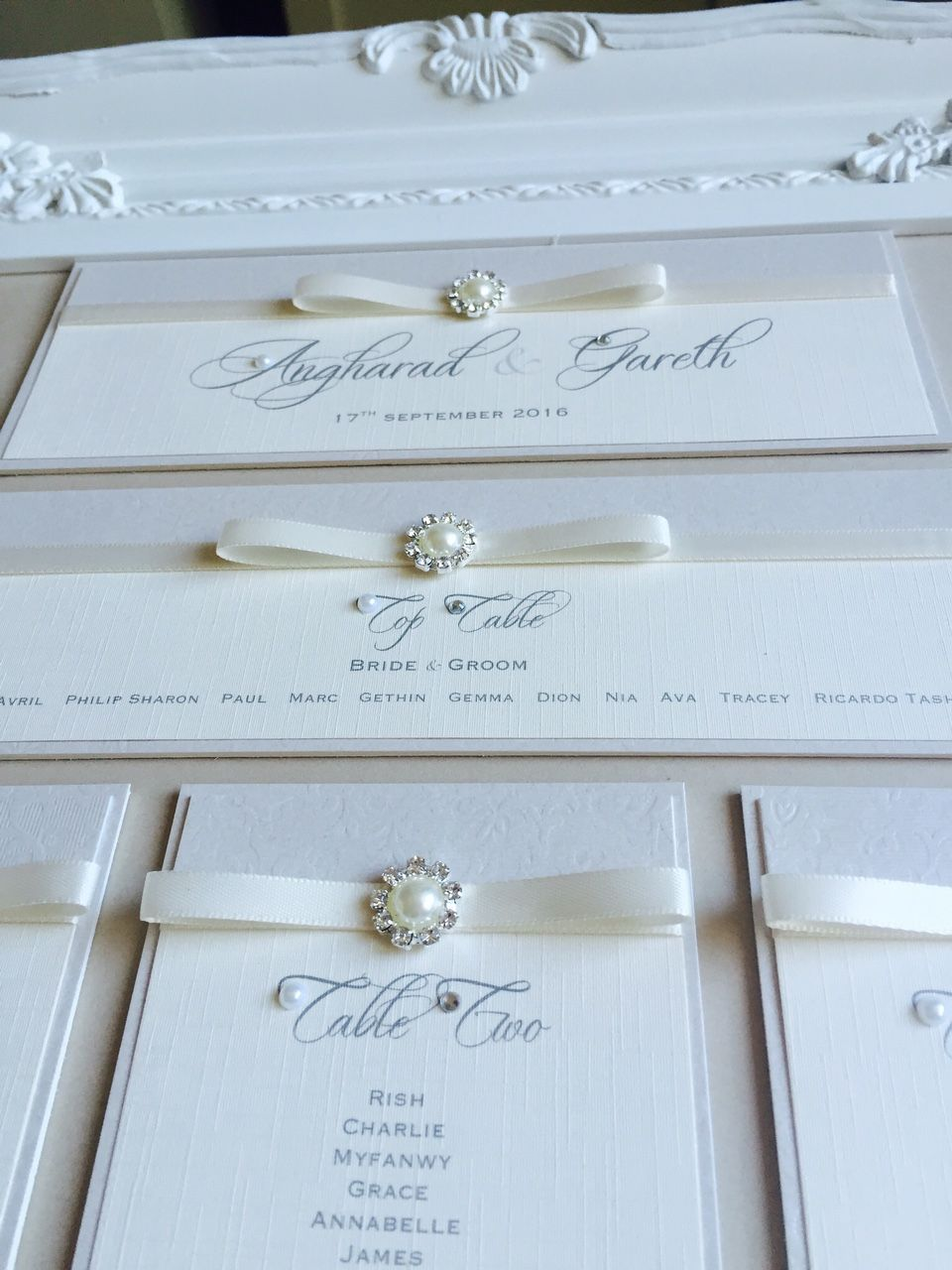 framed seating plan with pearls and ivory ribbon