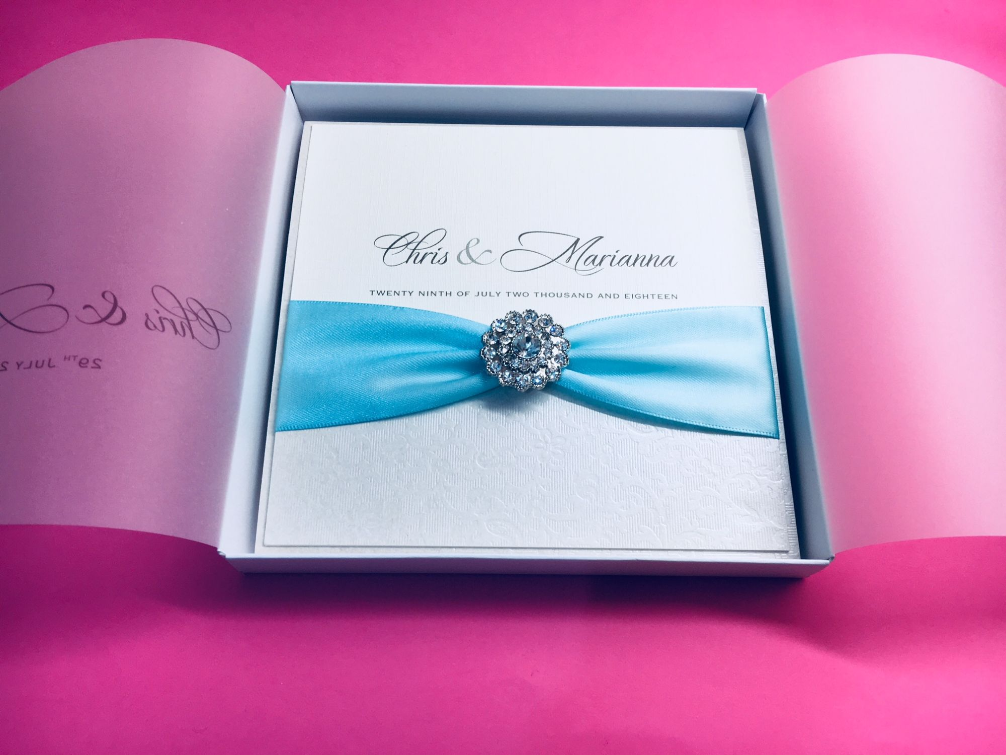 Romantic wedding invitation with aqua blue ribbon and crystal brooch presented in a box