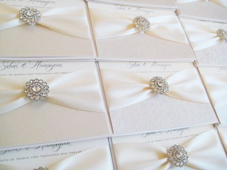 Romance ivory pocket style invitations with ivory ribbon and diamante brooch