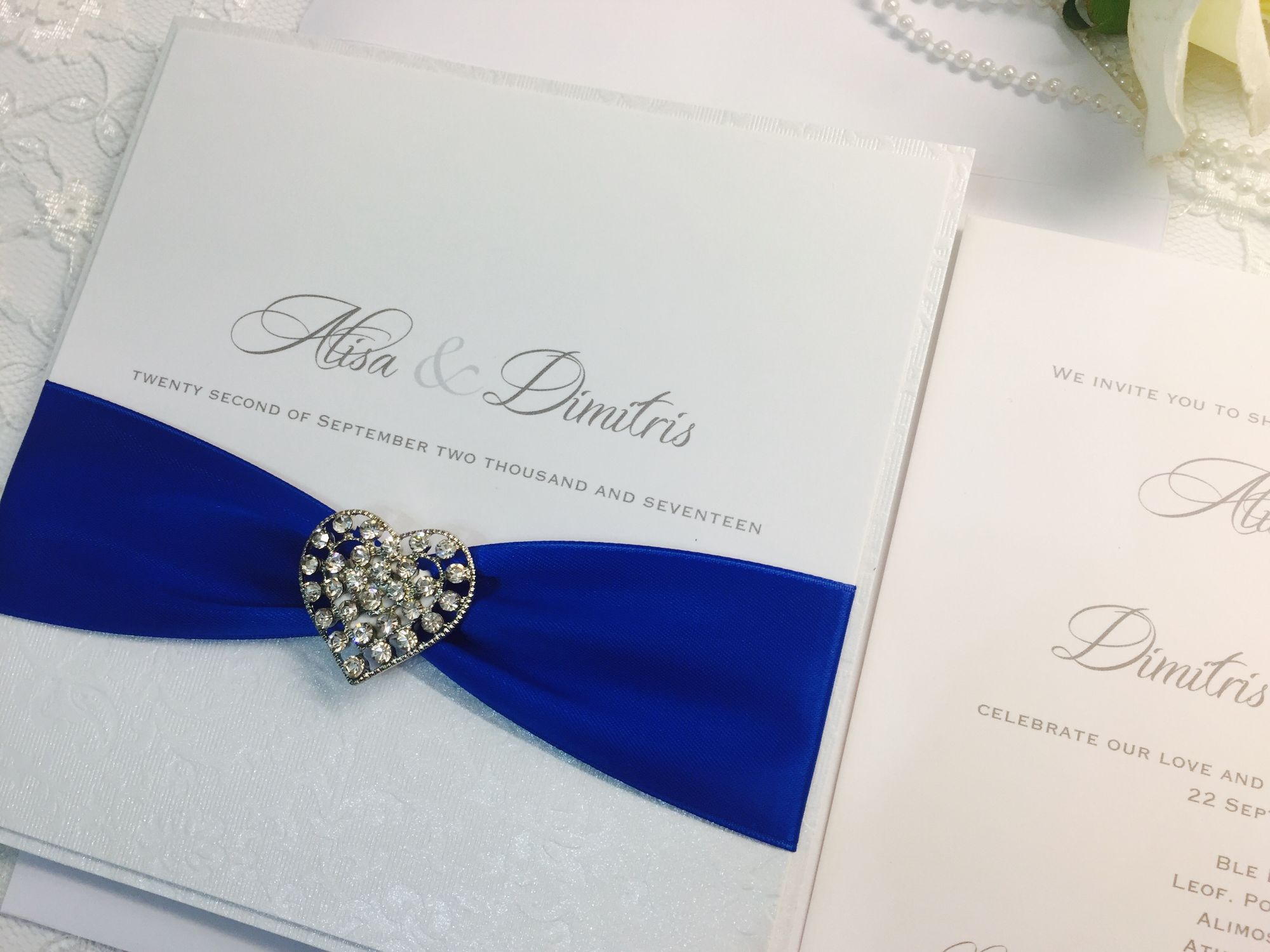 invitation with royal blue ribbon and vintage heart shaped brooch encrusted with diamante