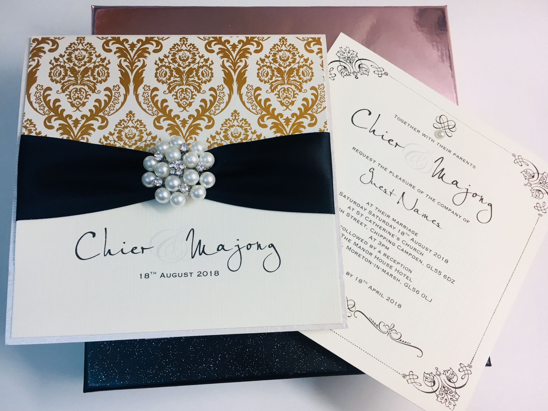 Beautiful gold and black wedding invitation with vintage pearl brooch