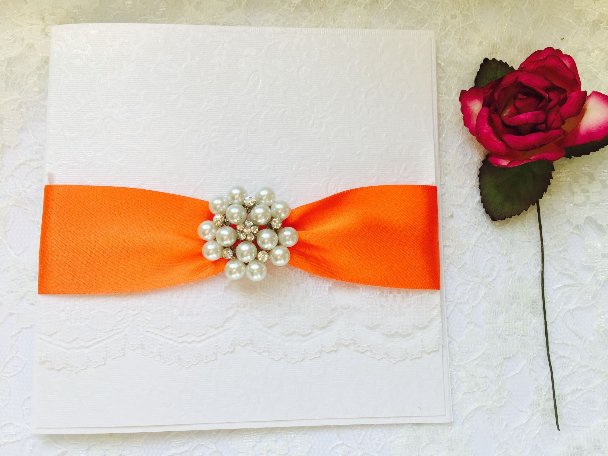 luxury boxed invitation with orange ribbon and white lace decorated with vintage pearl brooch