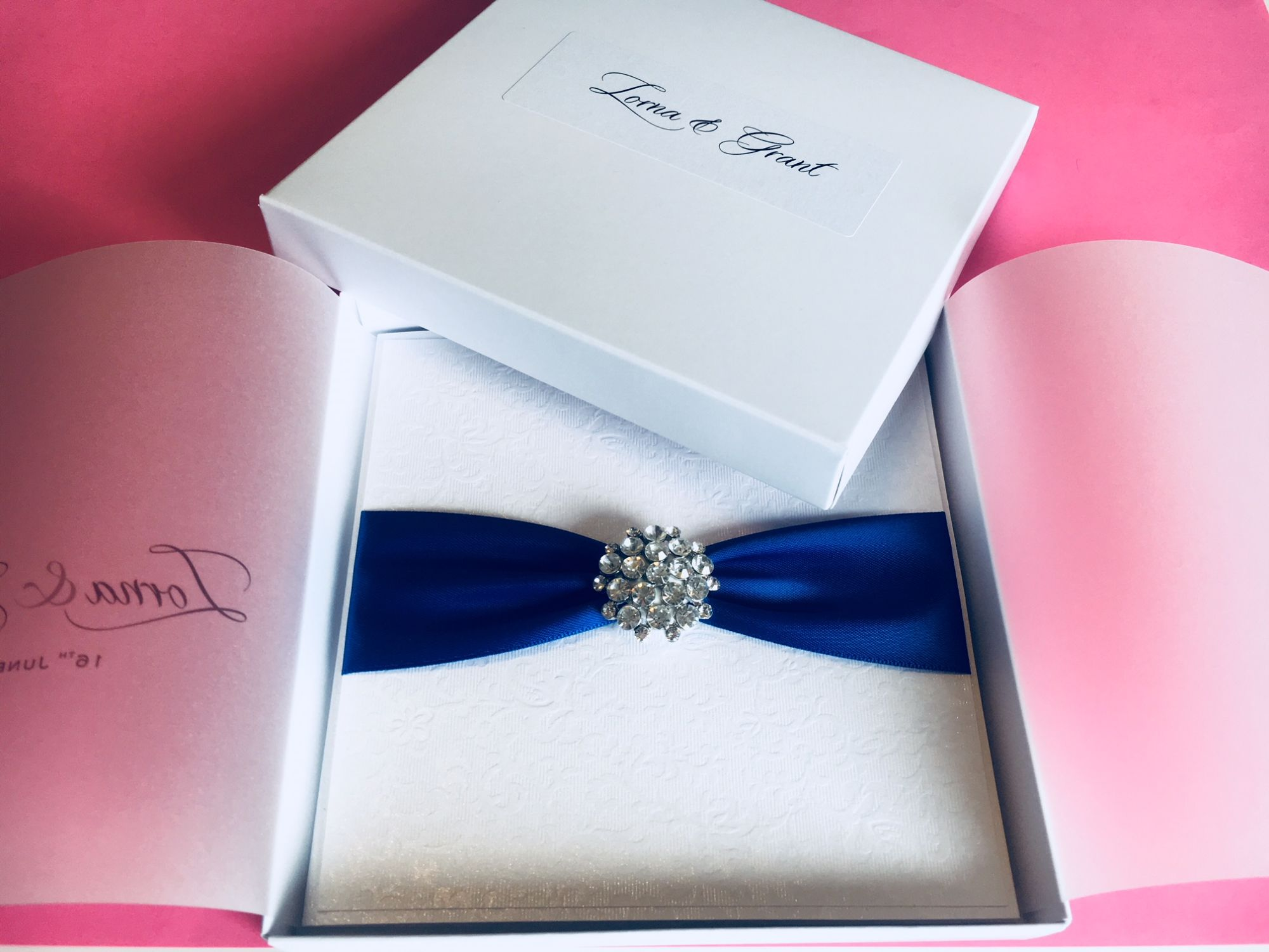 Boxed wedding invitation with royal blue ribbon and crystal brooch