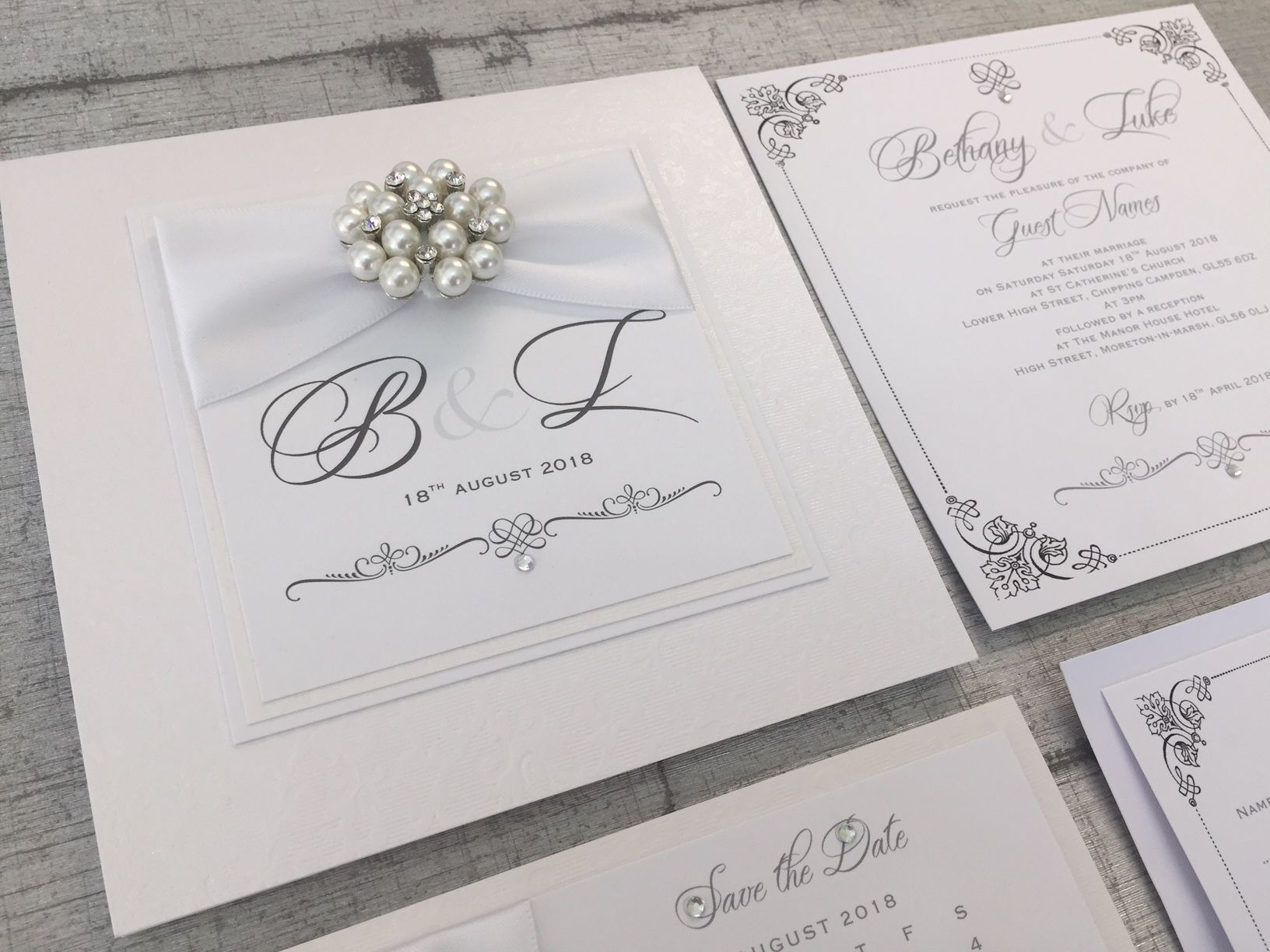 white monogram initials invitation in box with luxury vintage brooch