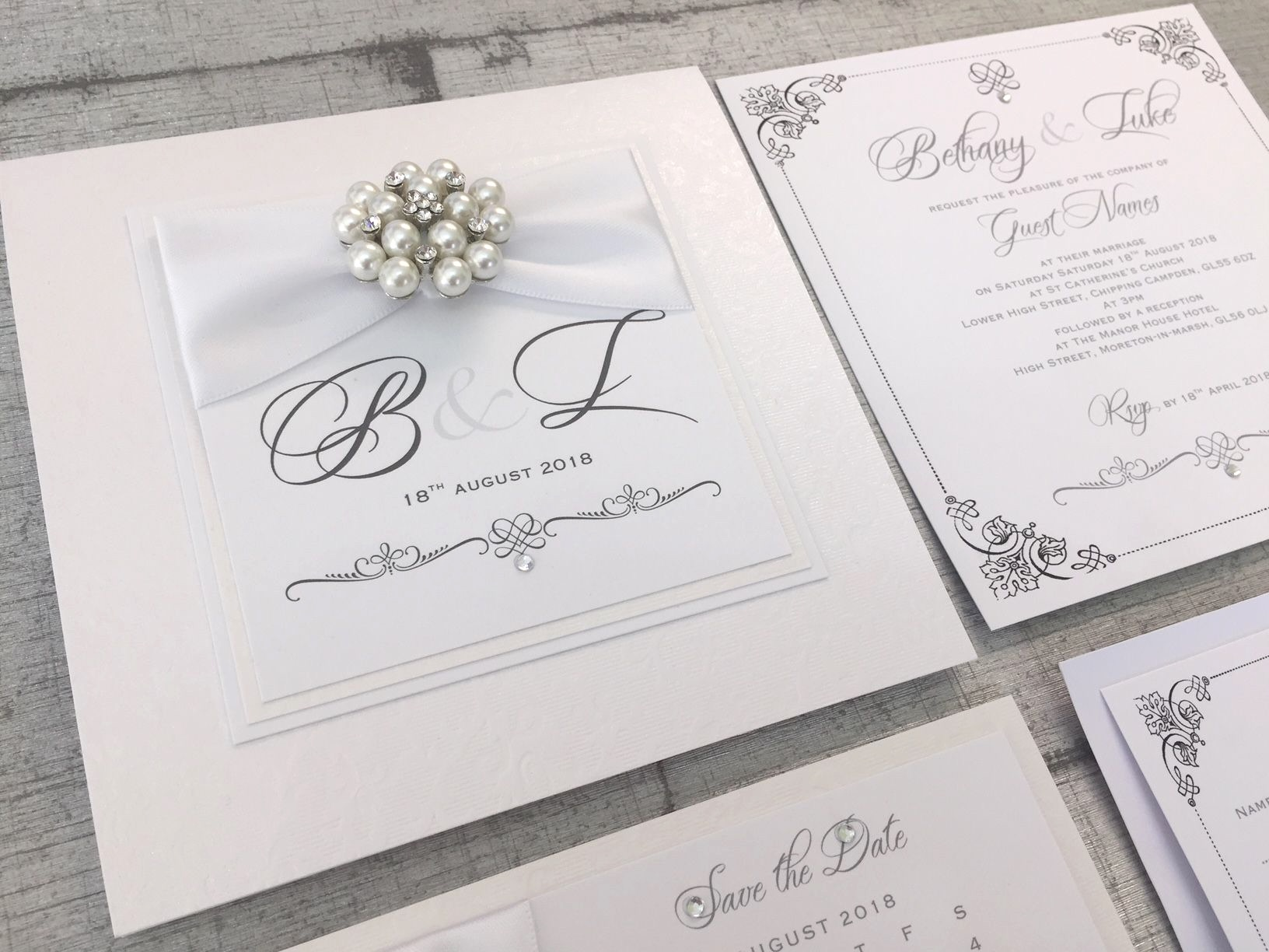 Boxed Monogram wedding invitations with white ribbon and beautiful brooch
