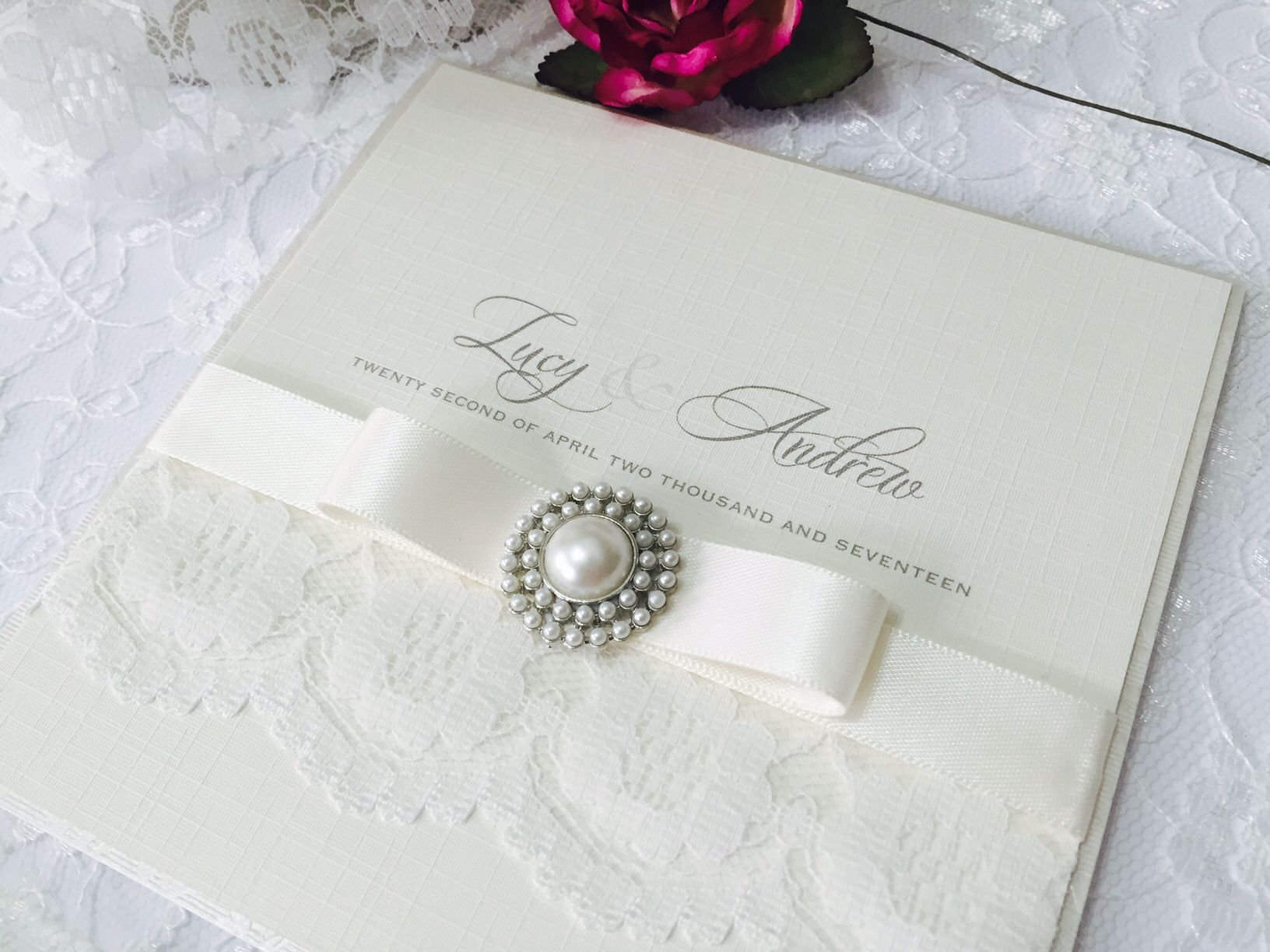Lace and ribbon wedding invitation decorated with a pearl brooch
