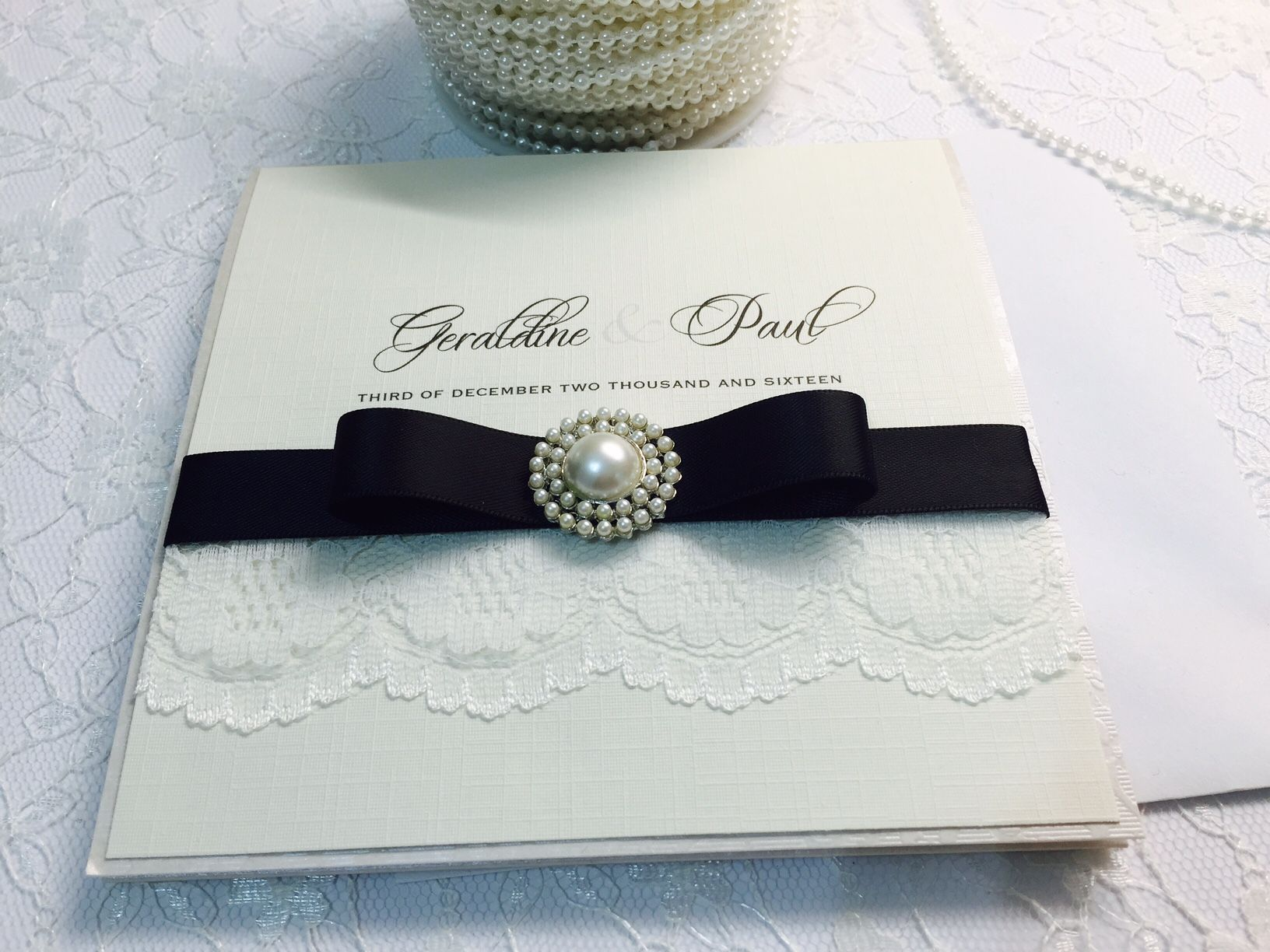 Ivory invitation with black bow and lace
