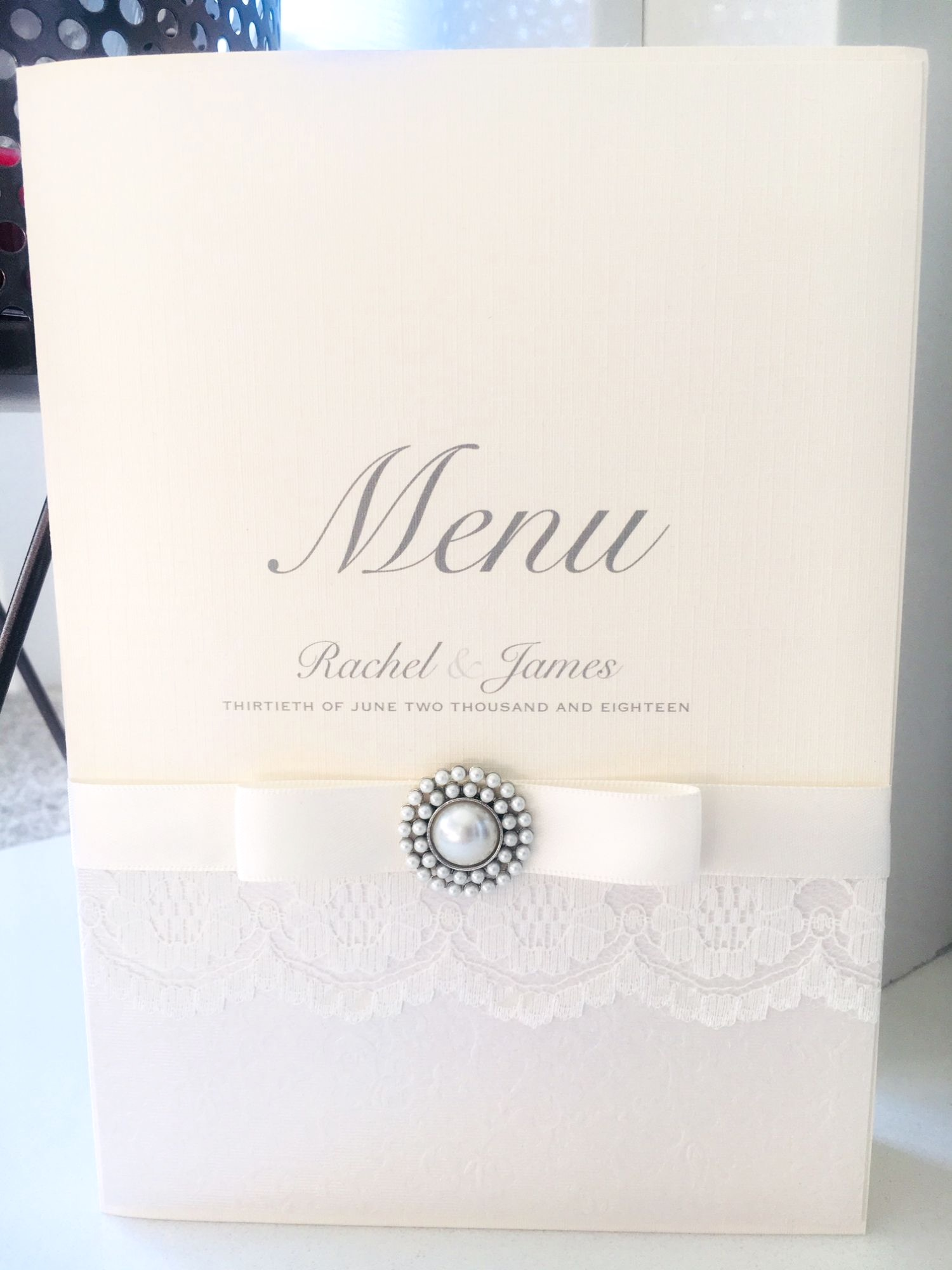 Luxury wedding breakfast menu with silver ribbon and vintage brooch