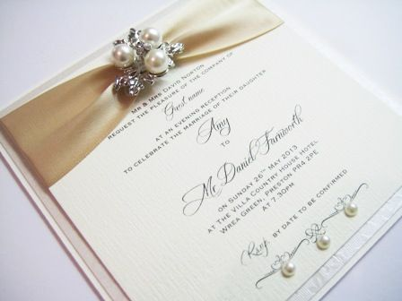 gold and ivory invitation with pearl brooch