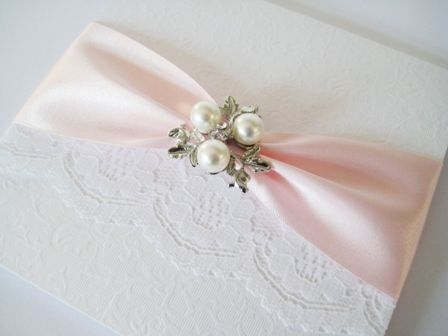 pale pink and lace wedding invitation with elegant brooch