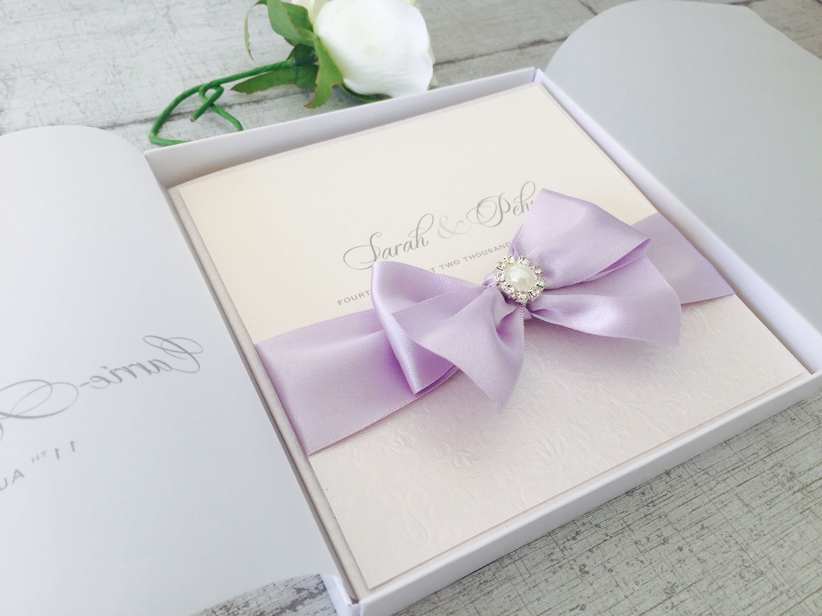 Boxed wedding invitations with big bows in box