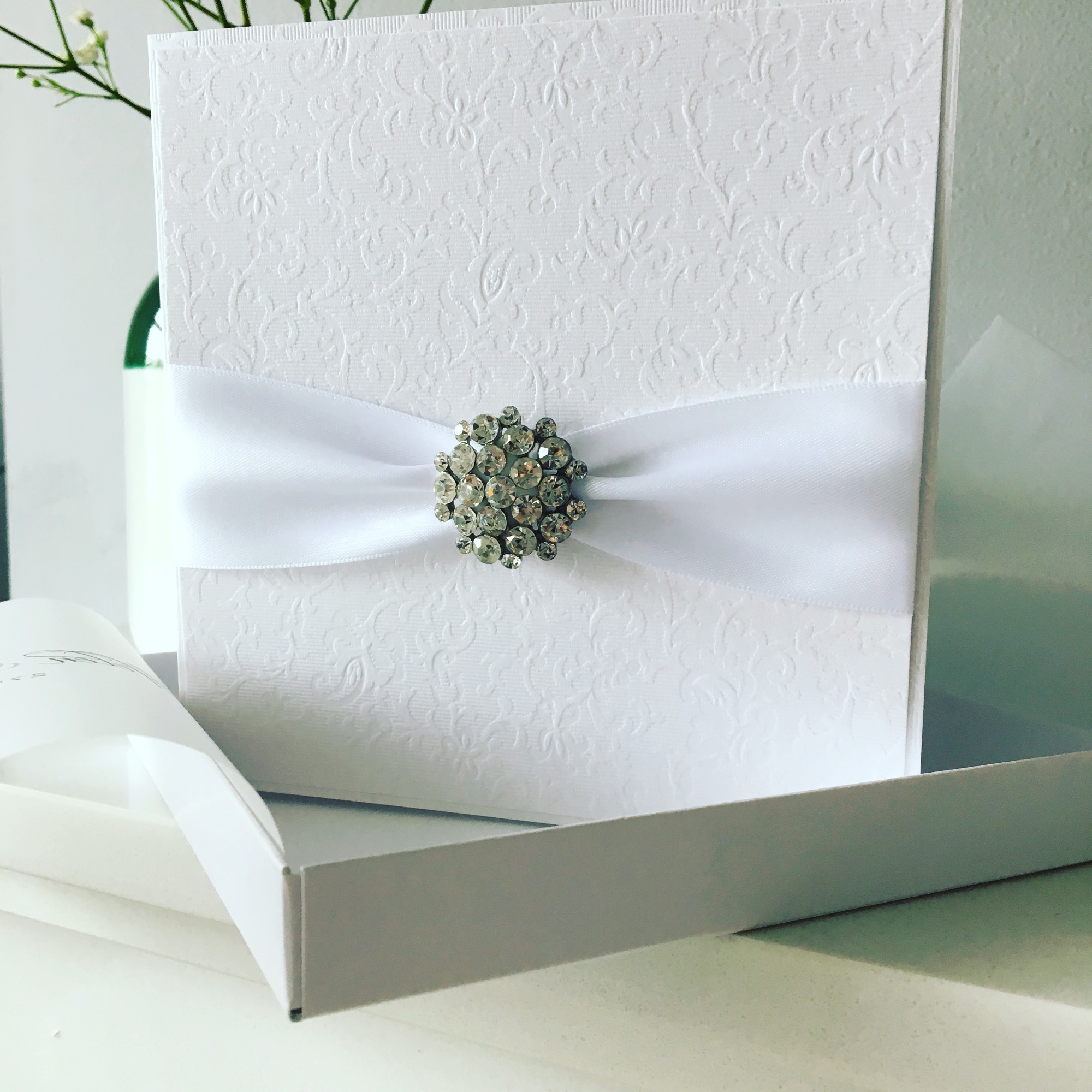 elegant boxed wedding invitation with white ribbon and diamante