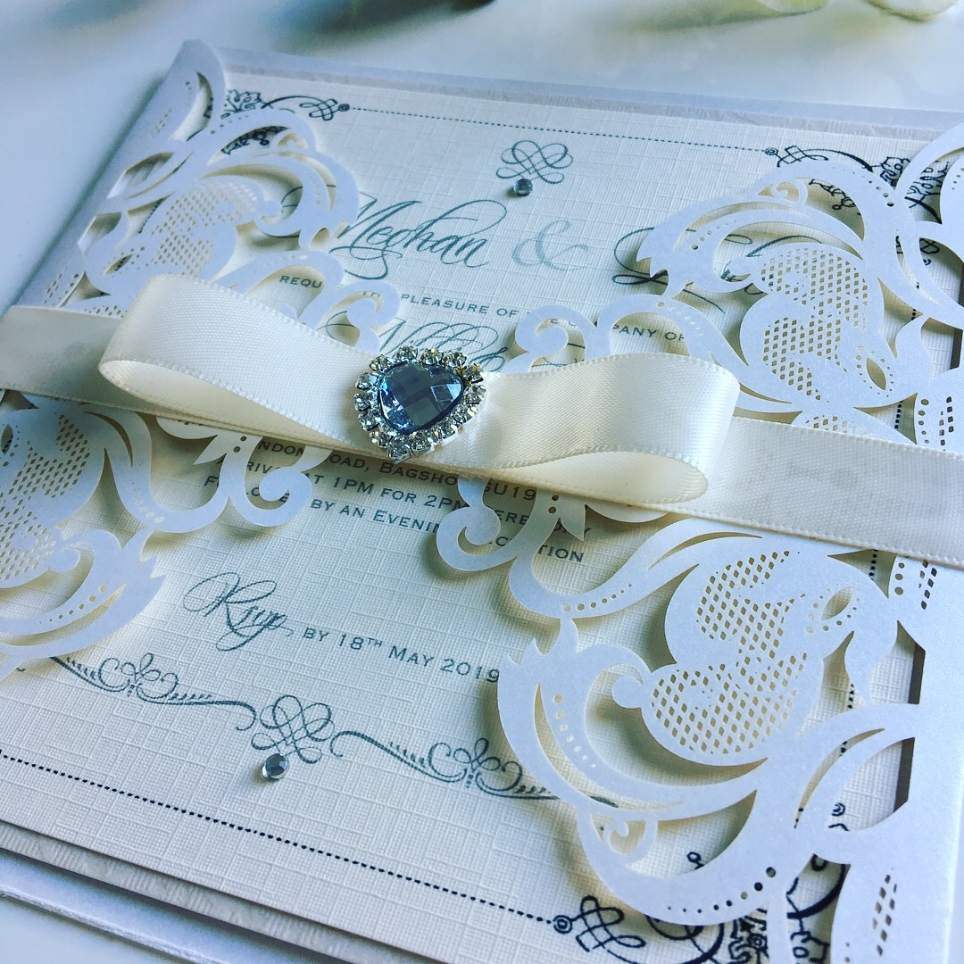 Laser cut wedding invitation with ribbon wrap and crystal heart brooch