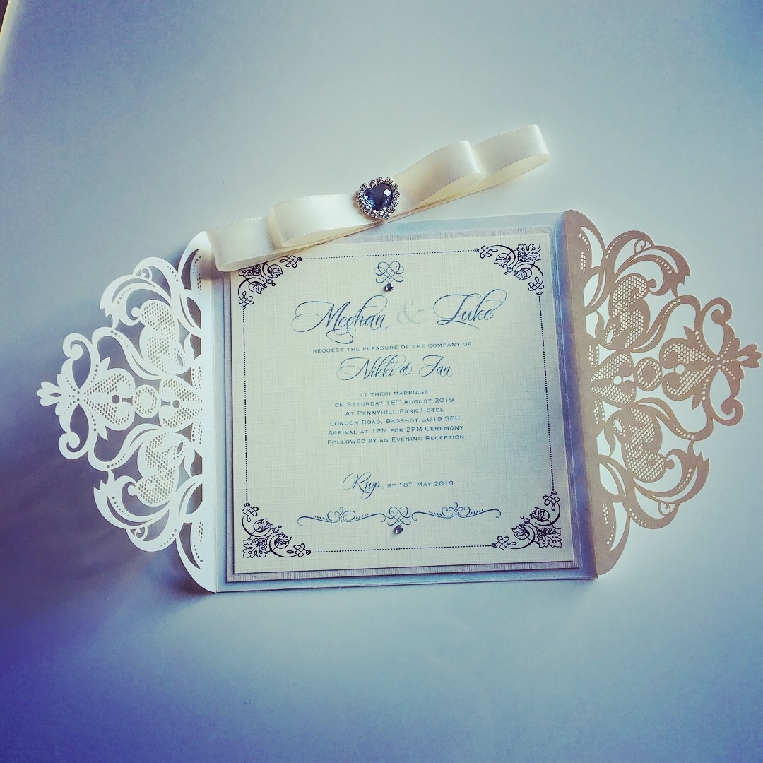 Laser cut pearlescent invitation with crystal heart bow