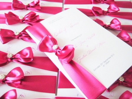 Order of service books with bow and crystal