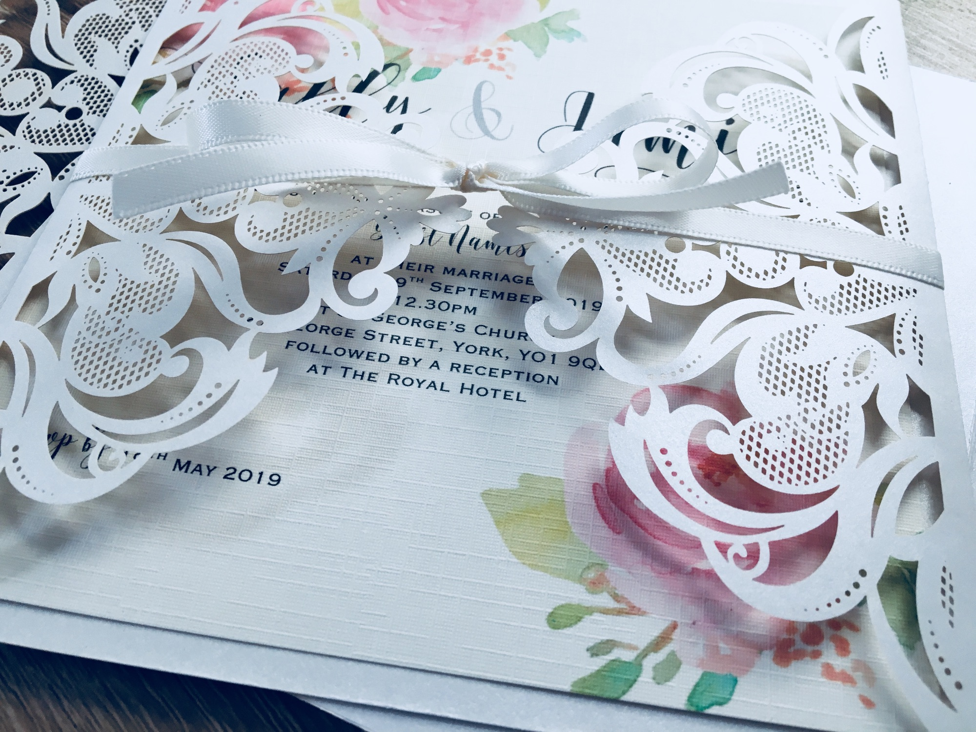 Ivory laser cut invitation with pink roses