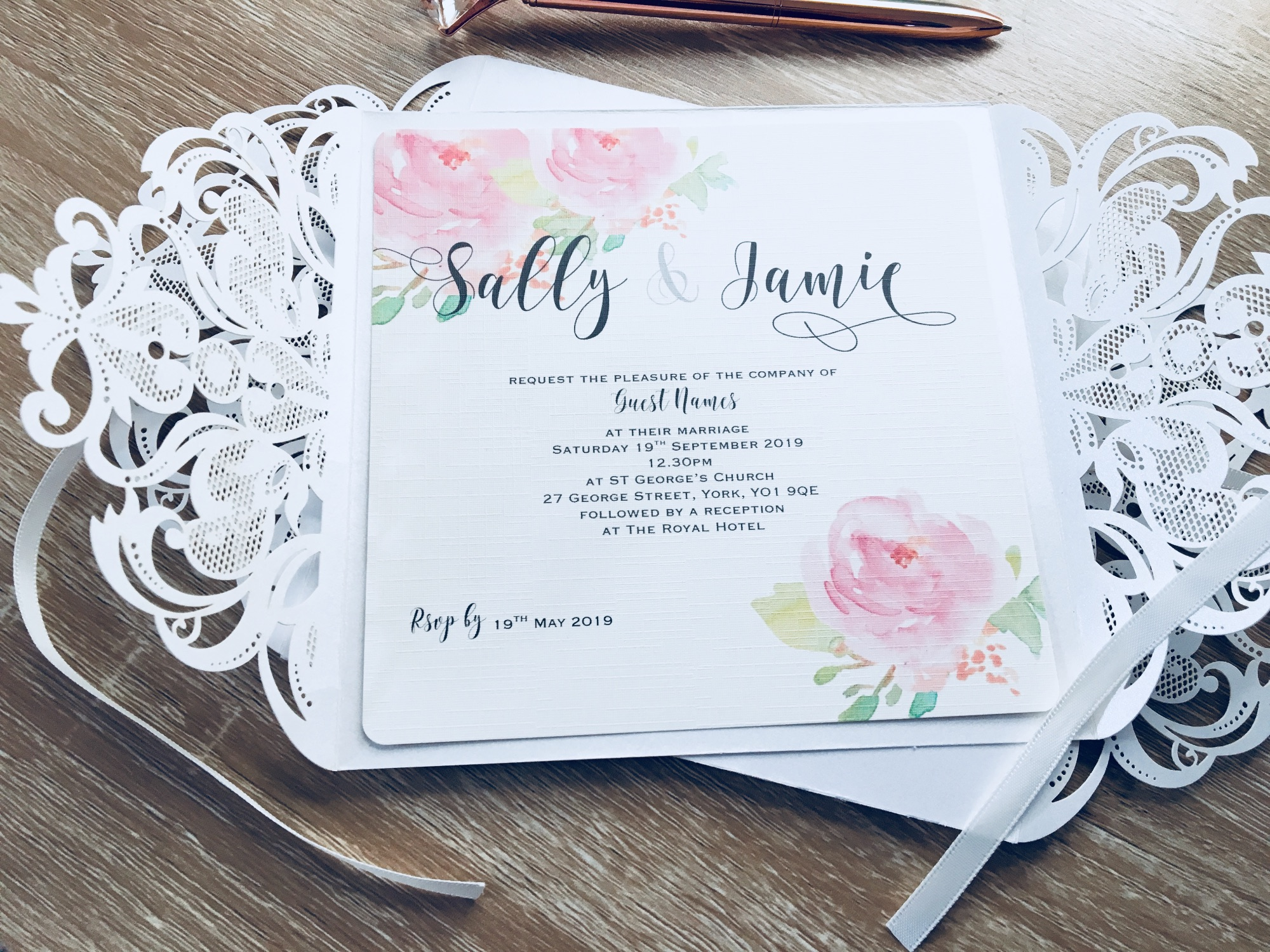 Laser cut invitations in box decorated with flowers and sparkles