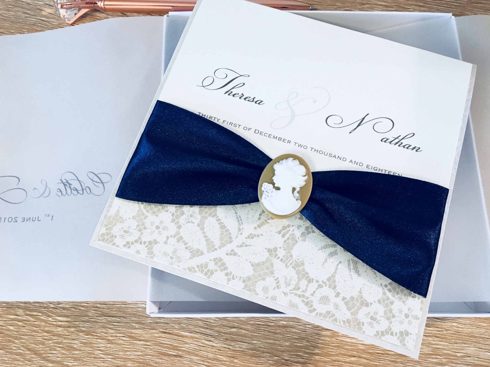 Cameo wedding invitation in box with navy ribbon