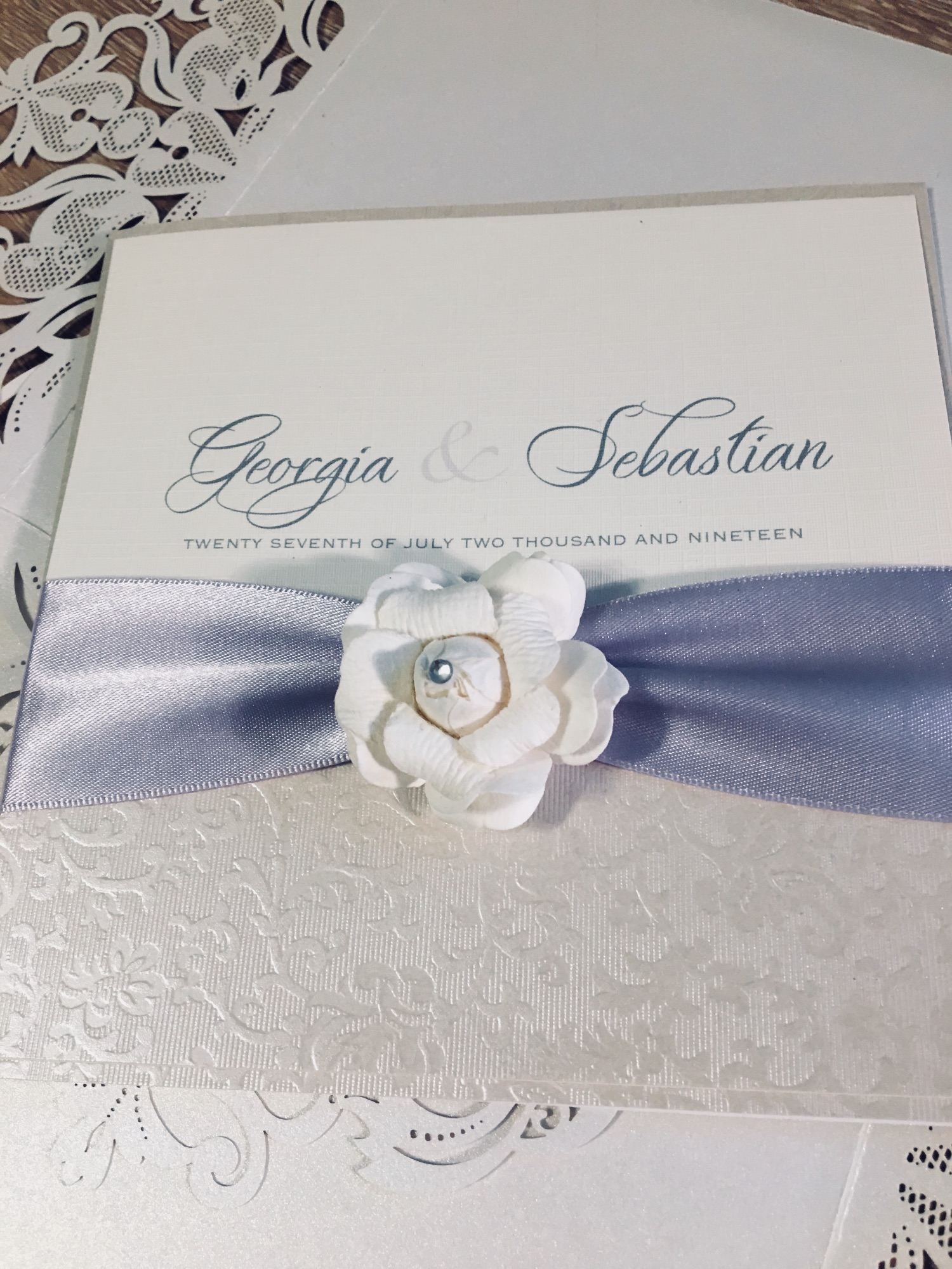 Beautiful rose wedding invitation in box with lilac ribbon and ivory rose