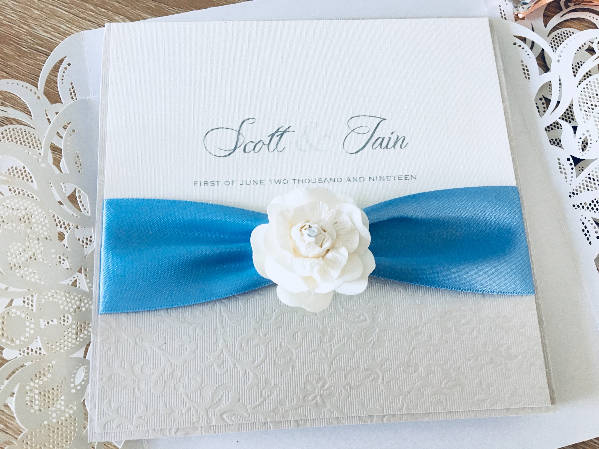 Rose boxed wedding invitation with pale blue ribbon and ivory rose