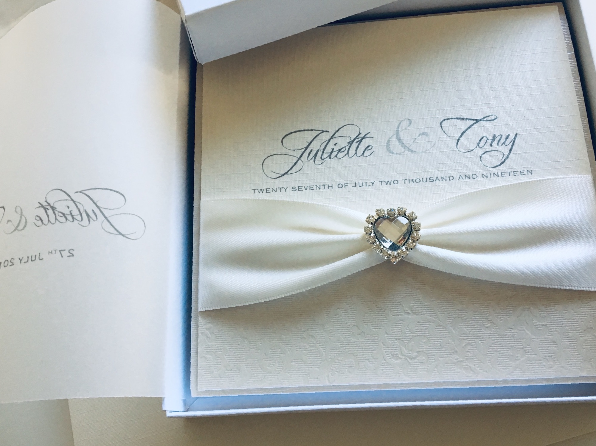 Boxed wedding invitation with ivory ribbon and heart crystal