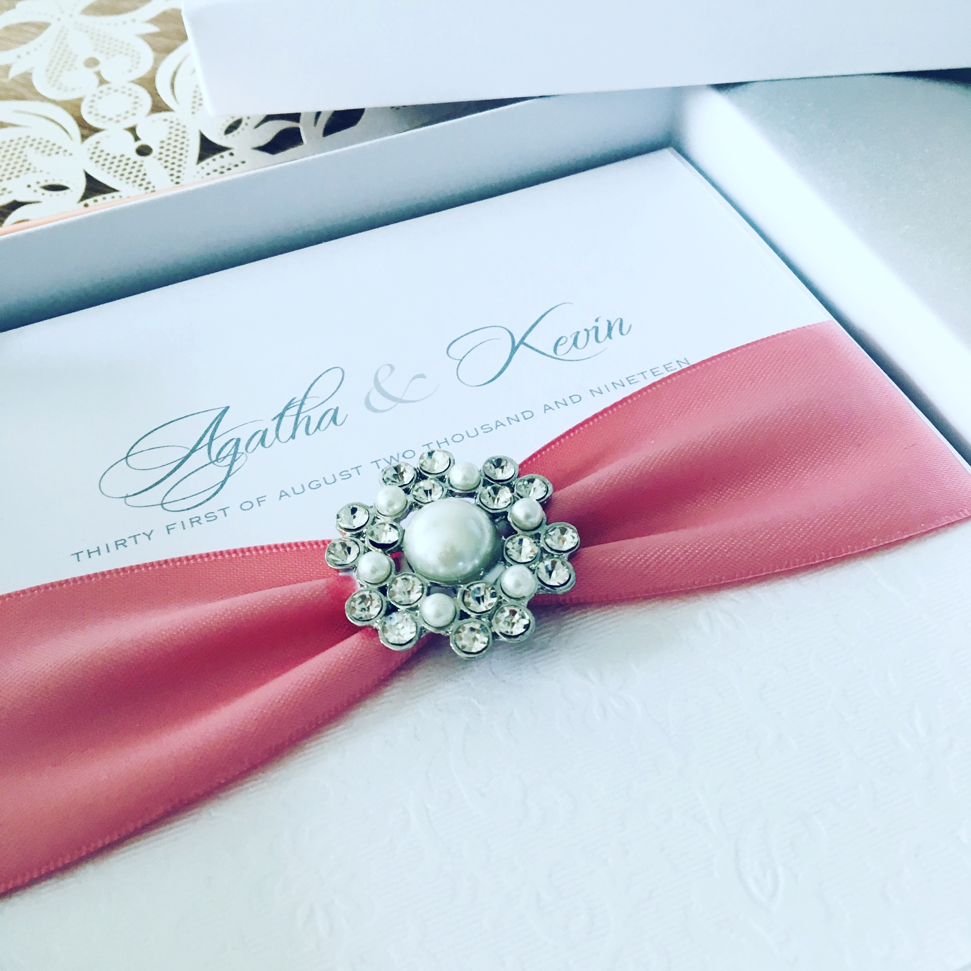Boxed luxury wedding invitation with dusky pink ribbon and pearl brooch