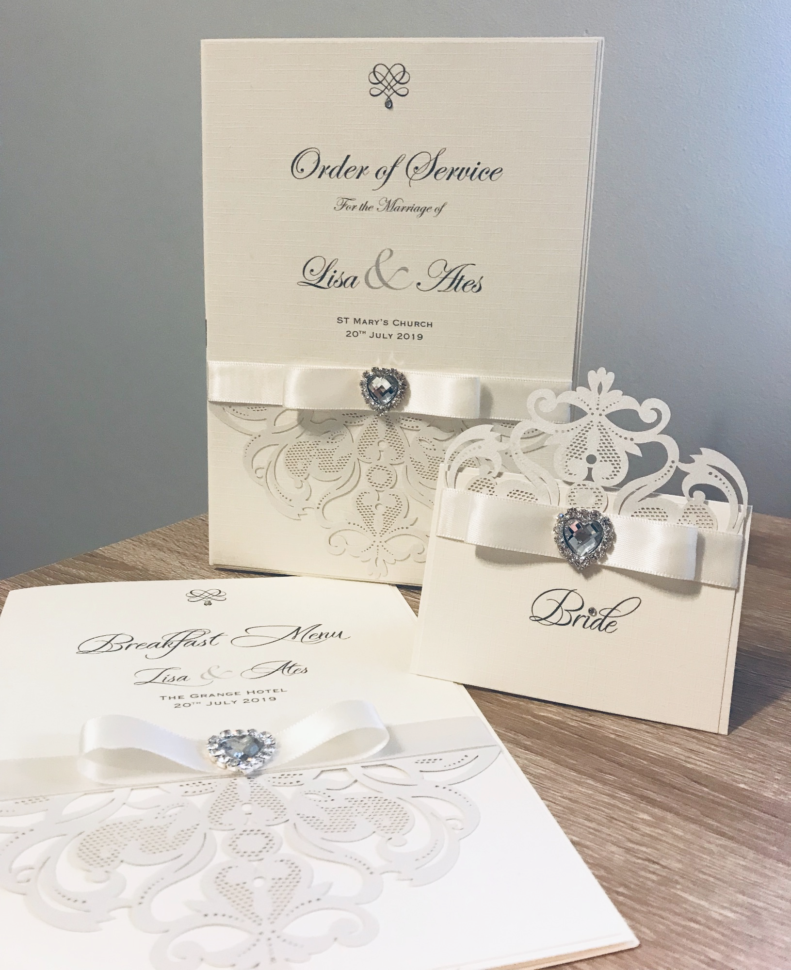 Order of service mass book in ivory with laser cut detailing and heart brooch