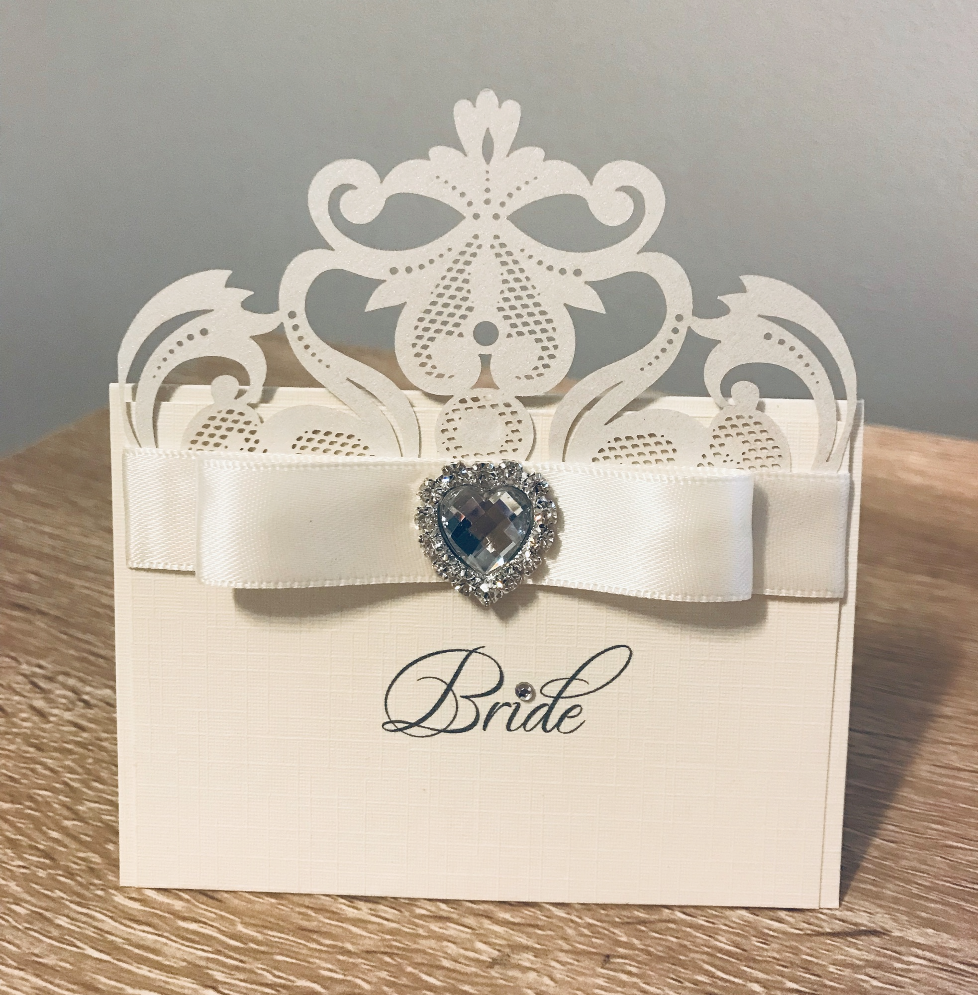 Laser cut place name card with ivory cream ribbon and heart brooch