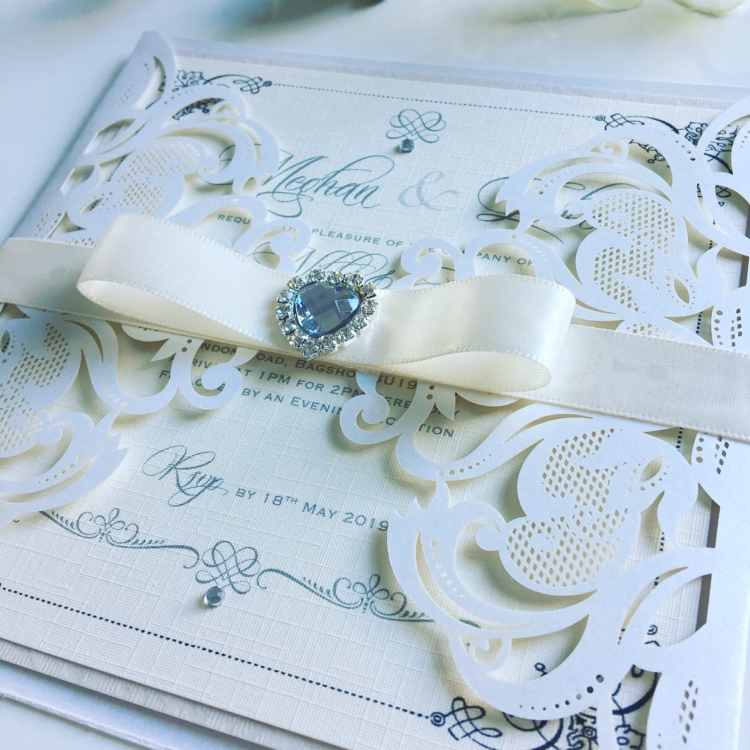 Laser cut wedding invitation with ribbon belly band and crystal heart brooch
