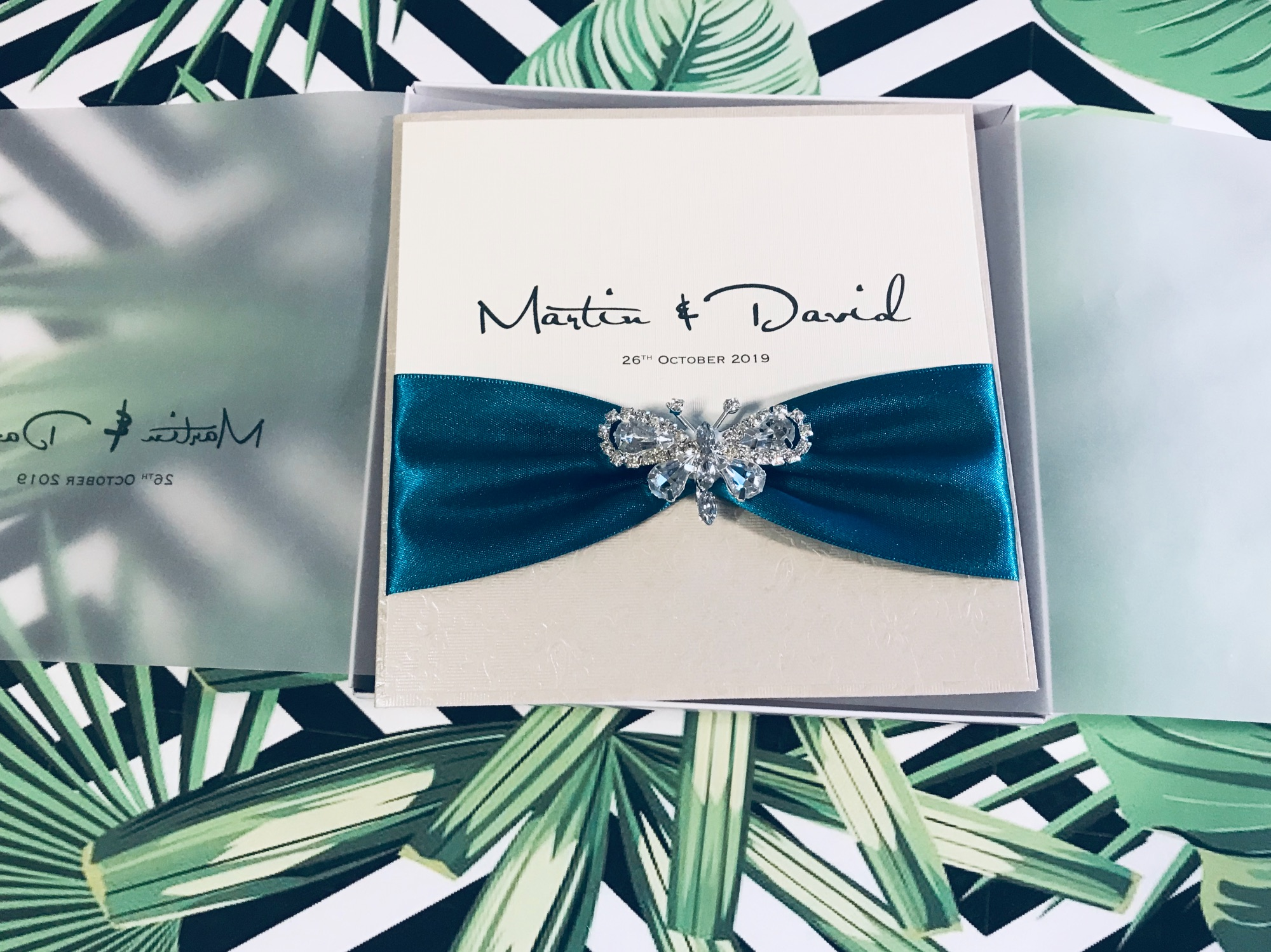 A Boxed butterfly wedding invitation with diamante butterfly brooch and ribbon