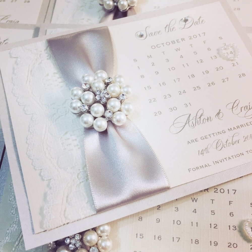 Beautiful save the date calendar card with a silver ribbon, lace and luxury pearl brooch