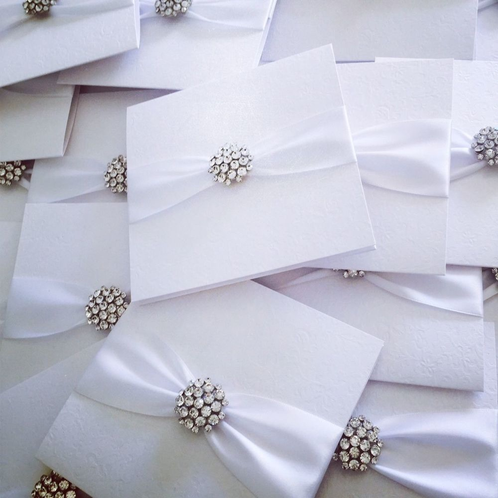 Boxed white wedding invitations with white ribbon and diamante brooch