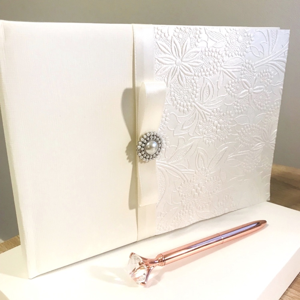 Ivory guest book with pearl brooch and ribbon