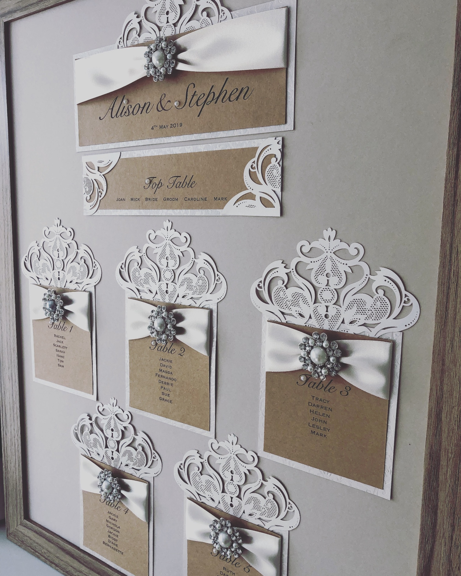 Rustic style seating plan with laser cut detailing and pearl brooch