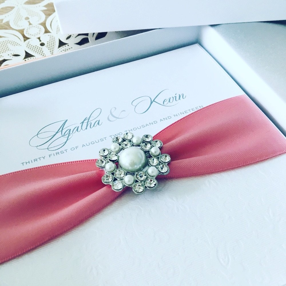 Luxury boxed pearl wedding invitation with dusky pink ribbon in box