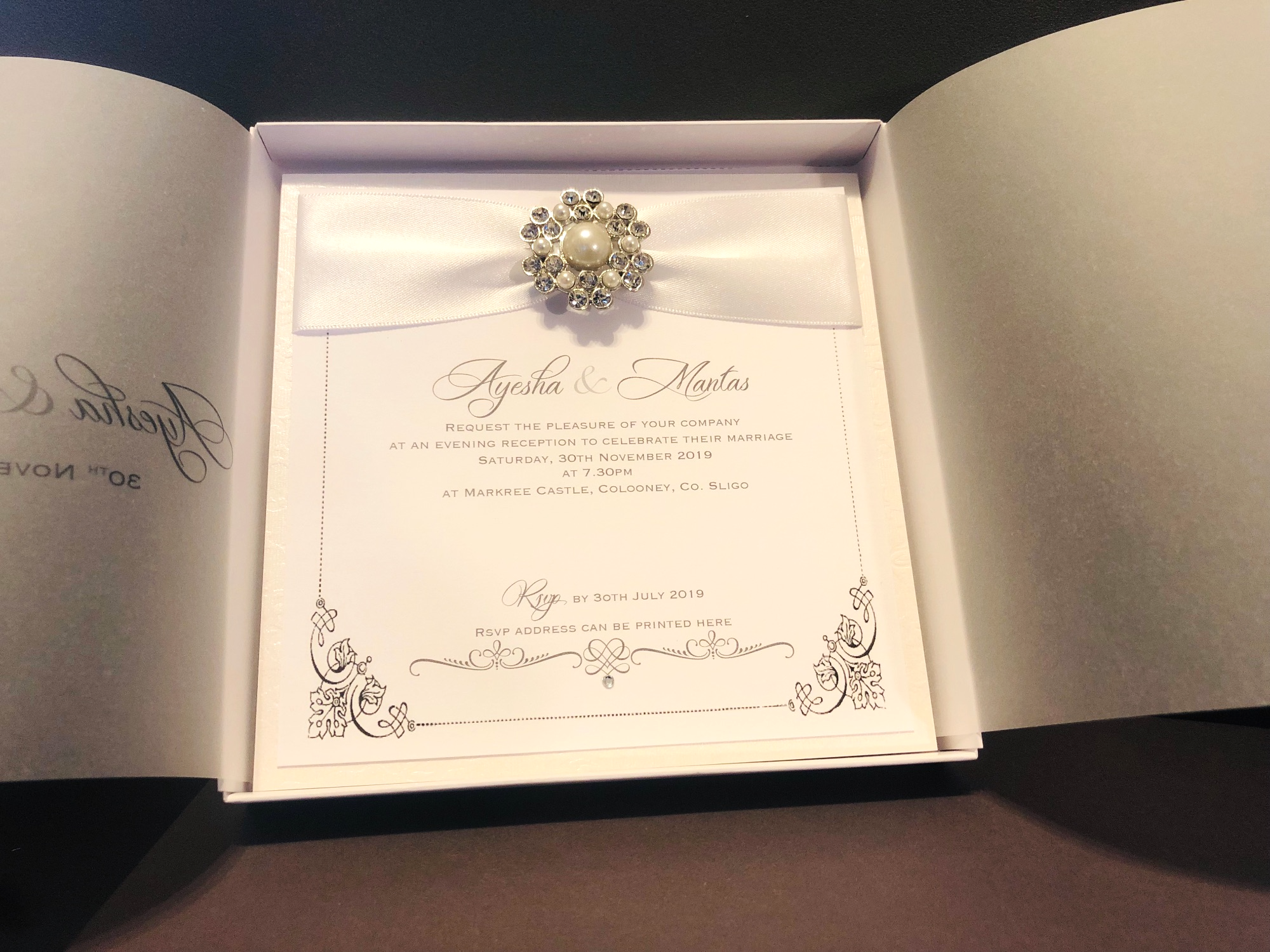 Luxury wedding invitation in box with pearl brooch and white ribbon